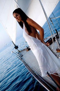 Glamorous female lifestyle model onboard a sailing yacht in the Mediterranean