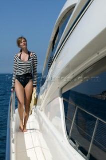 Woman in swimsuit standing on the side of a yacht.