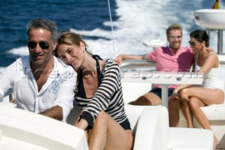 Four people sitting on top of yacht enjoying themselves.