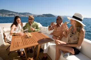 Four people sitting on a yacht drinking champagne