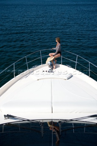 Woman sitting on the bow of a powerboat