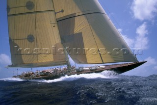 130 J-Class sloop, an elegant classic yachts, sails in a regatta under blue sunny skies.