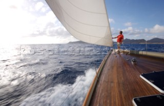 A man stands on the bow of the W-Class yacht Wild Horses near St. Bartholomew, French West Indies.