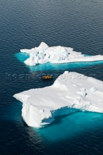Tourists on a motorized inflatable raft known as a zodiac, cruising amongst icebergs, Paradise Harbor, Danco Coast, Graham Land, Antarctica, on the 17 November 2008. Due to its picturesque landscape, with dramatic mountains and glaciers, Paradise Harbor is visited by numerous expedition cruise ships each Antarctic summer.