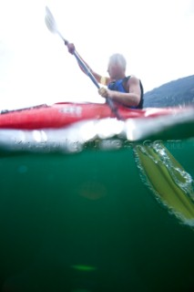 Over under water view of Patrick Orton paddling a sea kayak in Lake Pend Oreille near Sandpoint, Idaho