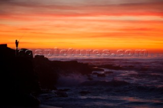 A lone fisherman stands on the rocky shore in La Jolla shore at sunset.  San Diego, California.