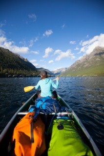 A woman in the bow of a fully loaded canoe, paddling across Bowman Lake in Glacier National Park, Montana.