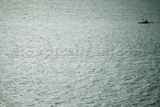 A lone sea kayaker paddles across the shimmering surface of Lake Pend Oreille in Sandpoint, Idaho