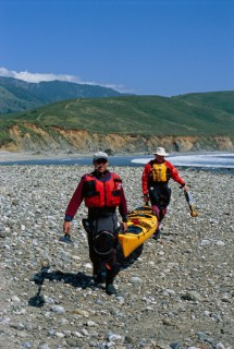 Writer Peter Heller and friend Landis Arnold portage their sea kayak along the beach at Andrew Molera State Park toward the mouth of the Big Sur River along the central coast of California.