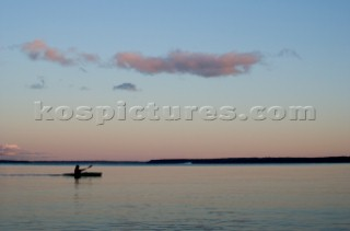 A sea kayaker paddles across Sebago lake at dusk on the outskirts of Portland Maine.