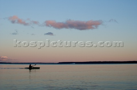 A sea kayaker paddles across Sebago lake at dusk on the outskirts of Portland Maine