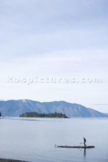 Woods Wheatcroft stops on a tiny rock island while sea kayaking on Lake Pend Oreille near Sandpoint, Idaho.