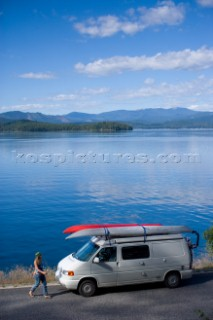 Holly Walker takes a break along the shoreline of Priest Lake on a road trip in northern Idaho. The image shows Walker walking back to her camper van loaded with sea kayaks and bikes. Priest Lake, Idaho.