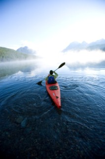 Andy Fueling paddles his kayak alone at dawn on Bowman Lake in Glacier National Park, Montana