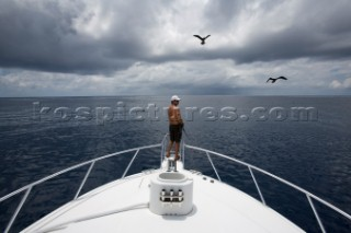 Wide view of a man fishing off the bow of a boat with a bird and dark clouds overhead in Costa Rica.