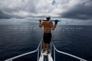 A man with a fishing pole resting on his shoulders, looking out at the ocean with dark clouds overhead in Costa Rica.