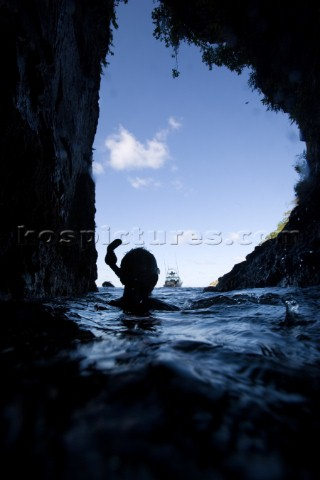 A cave diver looking out at a boat through an opening in the cave at the surface in Cocos Island Cos