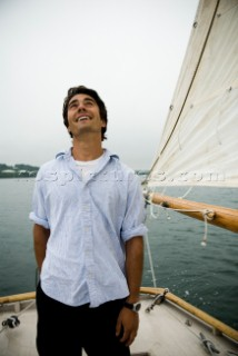 Man looking up at sails on sailboat, Casco Bay, Maine, New England. (releasecode: rausher and rausherPR)