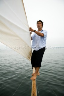 Man adjusts the sail on a sailboat, Casco Bay, Maine, New England. (releasecode: rausher and rausherPR)