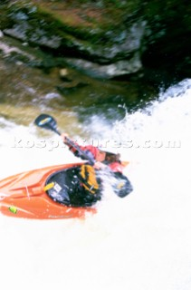 Kayaker Lane Jacobs takes a drop over a small waterfall on Cow Creek, northern Idaho. Every spring small creeks in northern Idaho near the Canadian border become runable. Kayakers from throughout the West make the trip to go. Woods Wheatcroft/Aurora Photos